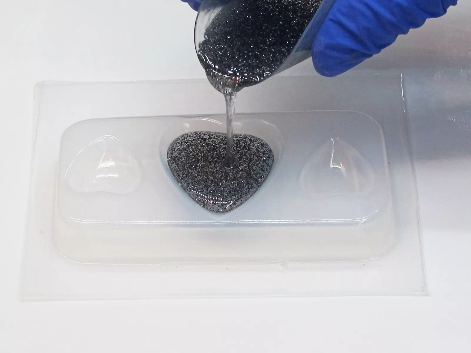 pouring resin into a plastic heart mold