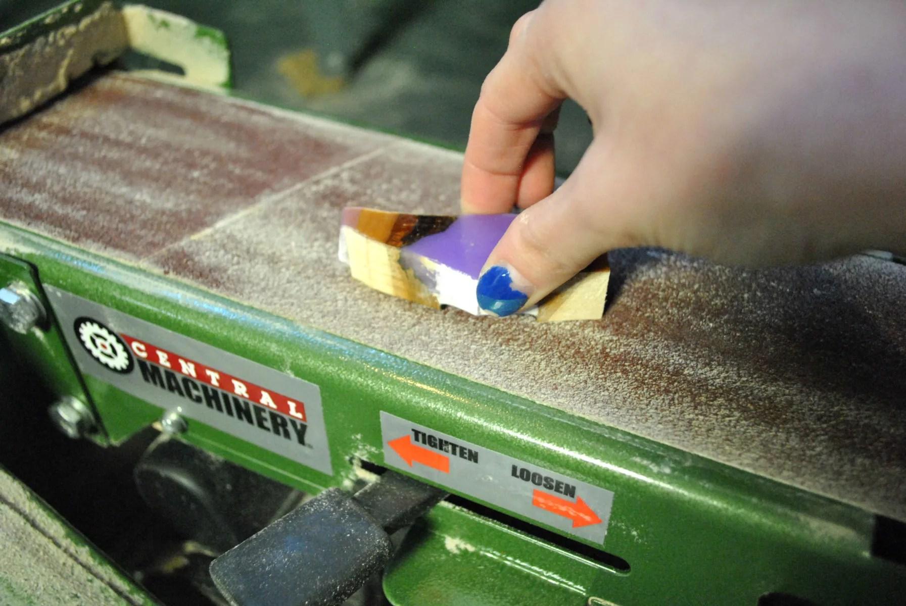 holding wood and lavender resin shard on belt sander surface