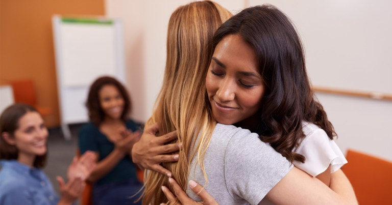 Two women in a women's group stand and share a hug, with the group sitting around them.