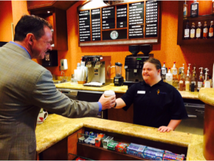 a woman with a disability working as a barista offers a customer a coffee as an example of the #RespectTheAbility campaign