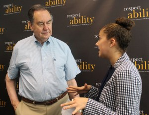 Cal Thomas talking with RespectAbility Fellow Brilynn Rakes in front of RespectAbility banner