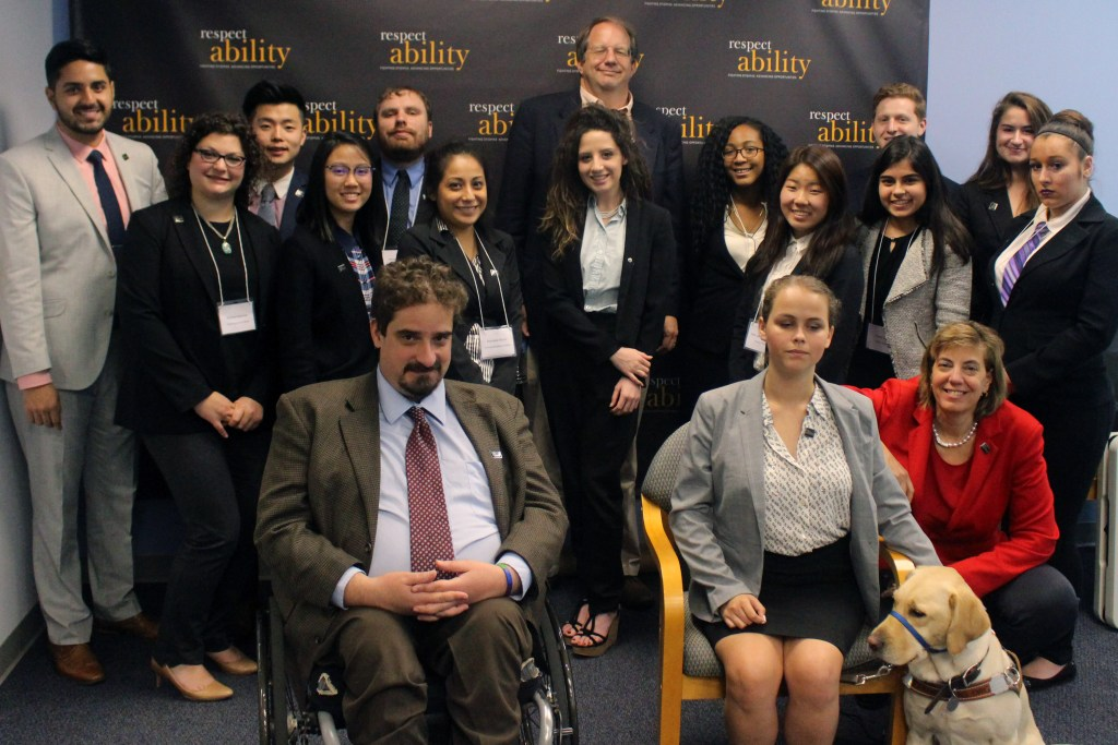 Dan Hazelwood and RespectAbility Fellows standing and seated in a posed photograph, smiling for the camera