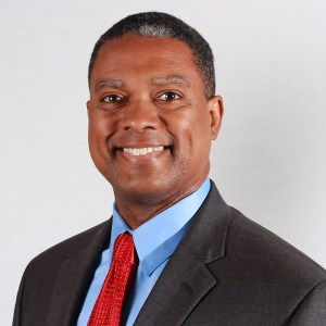 headshot of Gerard Robinson, wearing a gray suit, blue shirt and red tie