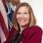Jennifer Sheehy official DOL Portrait wearing a red blazer sitting in front of two flags - American flag and DOL flag