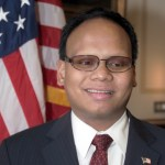Ollie Cantos smiling in an official portrait wearing a suit and American flag pin in front of an American flag