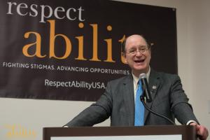 Brad Sherman speaking at the microphone with a RespectAbility banner behind him
