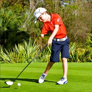 Tommy Morrissey, who has just one arm, golfing wearing blue shorts and a red collared shirt and baseball cap