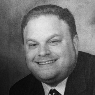 headshot of Aaron Orlofsky smiling and squiting eyes, wearing suit and tie grayscale photo