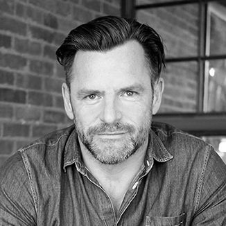 headshot of Andrew Egan leaning on a table wearing a button down shirt and facing the camera grayscale photo