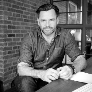 Andrew Egan leaning on a table wearing a button down shirt and facing the camera grayscale photo