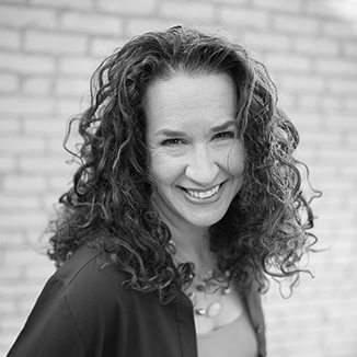 headshot of Dana Marlowe smiling at the camera she has long curly hair grayscale photo
