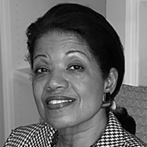 headshot of Janie L. Jeffers smiling and wearing lipstick, earrings, and a patterned jacket grayscale photo