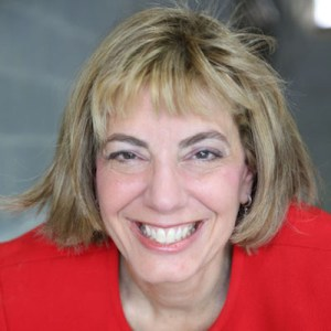 Headshot of Jennifer Mizrahi, smiling and facing the camera wearing a red blazer color photo