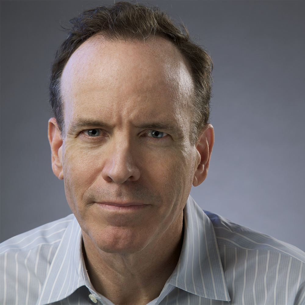 headshot of Jonathan Murray wearing a gray striped shirt and facing the camera color photo