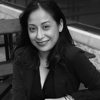 Marisela is sitting on bench smiling with a black dress and black blazer on grayscale photo