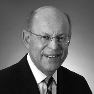 headshot of Ronald Glancz wearing glasses and a blue tie grayscale photo