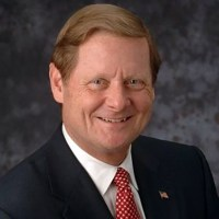 Steve Bartlett, has brown hair and he is smiling and wearing a black suit, white shirt, and red spotted tie and an american flag pin on his jacket, color photo