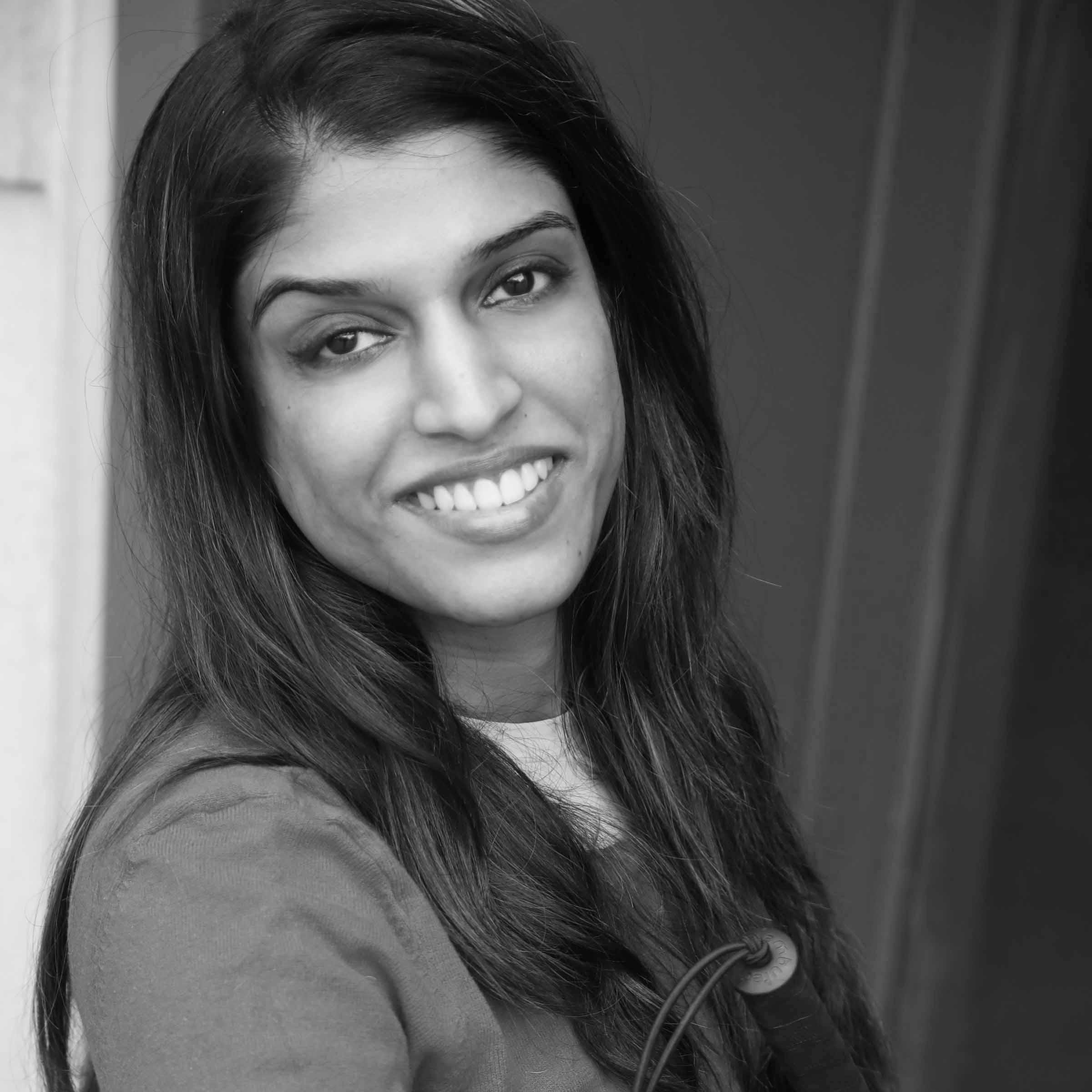 Headshot of Khadija Bari smiling leaning against a wall