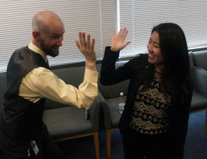 Murray and Policy Fellow, Ana Song doing funny poses and reaching their hands together like they are about to do a high five. Ana is and Murray are smiling.