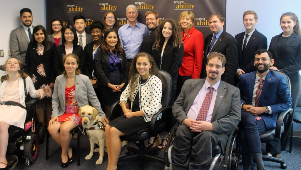 Richard Wolf pictured with RespectAbility Fellows and staff seated and standing in front of a RespectAbility banner