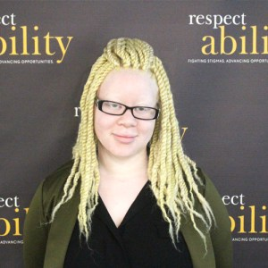 RespectAbility fellow Katie Townes smiling in front of the RespectAbility banner