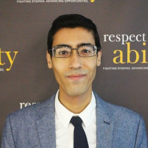Adam Srayi standing in front of the RespectAbility logo smiling