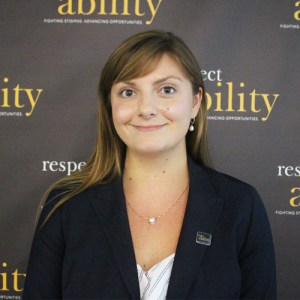 RespectAbility Fellow Julia Wood smiling in front of the RespectAbility banner
