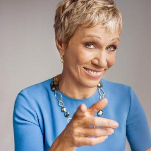 Barbara Corcoran pointing toward the camera wearing a blue top and silver necklace