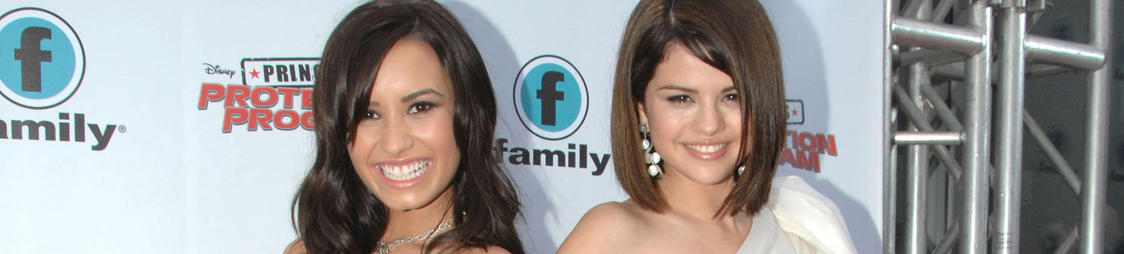 Demi Lovato and Selena Gomez smiling and posing for the camera, Demi in black dress and Selena in a white dress