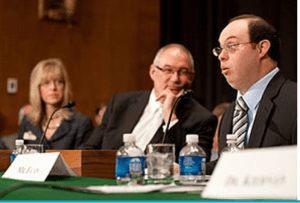 Egan seated behind a table with other panelists, with bottles of water and nameplates in front