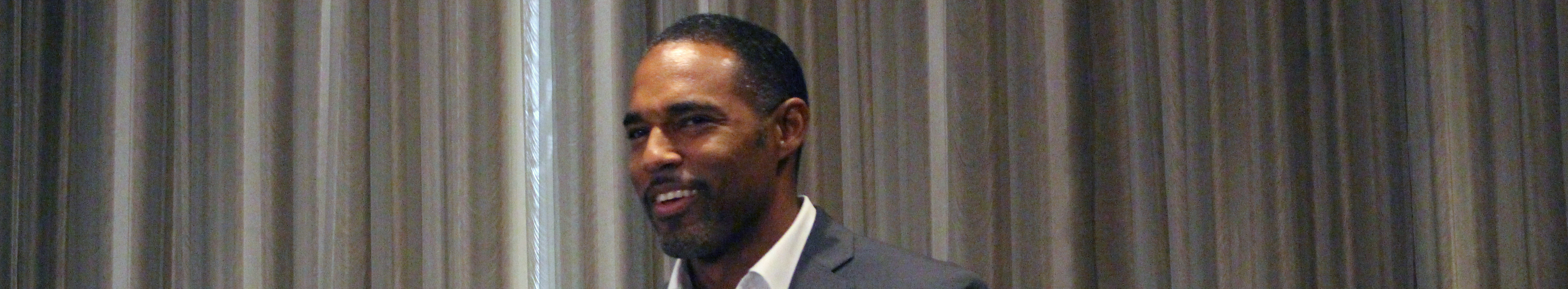 Jason George standing at a podium with the sign Media Access Awards