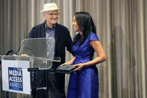 Norman Lear with his hand on host Haben Girma's shoulder, speaking behind the podium