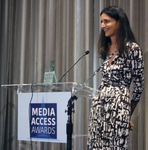 Atypical's Robia Rashid standing at a podium with the sign Media Access Awards