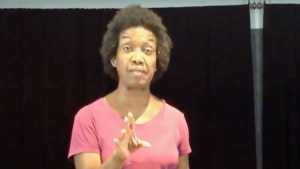 Diana Elizabeth Jordan wearing a pink shirt speaking on stage