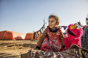 A young girl engages with Elmo at an informal tented settlement near Mafraq, Jordan, in February 2017