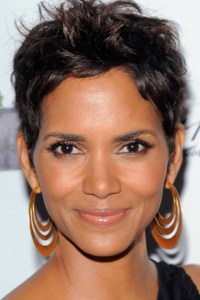 Halle Berry headshot smiling facing the camera with gold hoop earrings