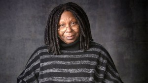 Whoopi Goldberg wearing a black and gray striped sweater facing the camera