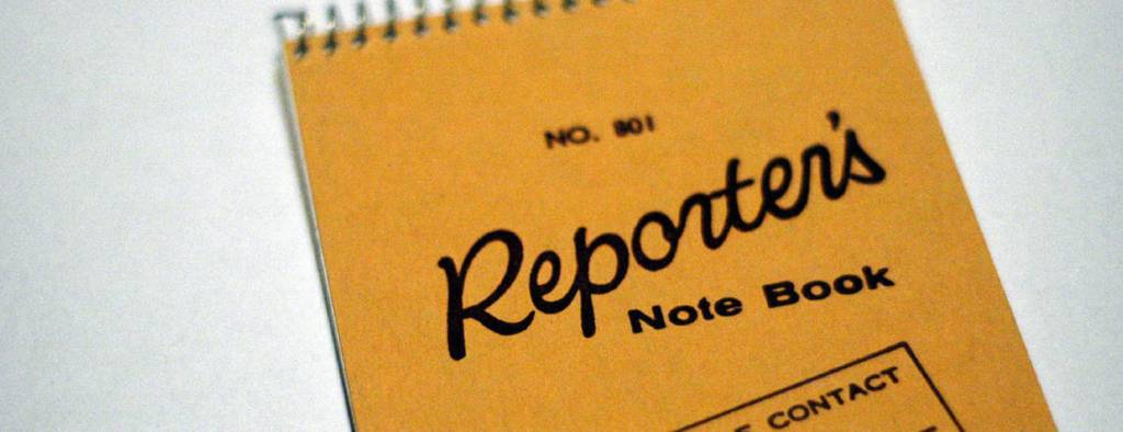 """A notebook that says """"Reporter Note Book"""" on the cover"""