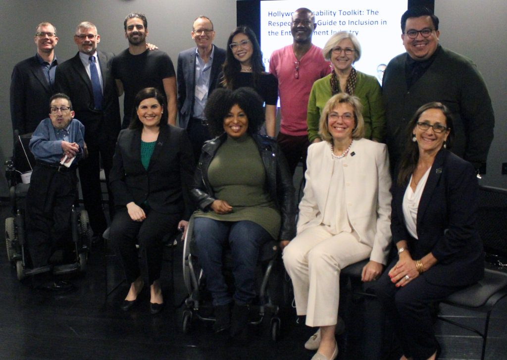 A group of people seated in chairs and wheelchairs and standing smiling and posing for the camera