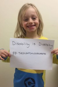 "Maisie Sly smiling and holding a sign that reads ""Disability is Diversity #thesilentchildoscars90"""