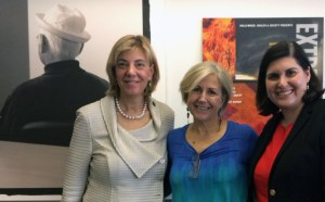 HH&S' Director Kate Folb in between RespectAbility's President Jennifer Laszlo Mizrahi and Communications Director Lauren Appelbaum, all standing and smiling, in front of a picture of Norman Lear