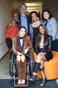 five diverse women and one man standing and seated smiling for the camera