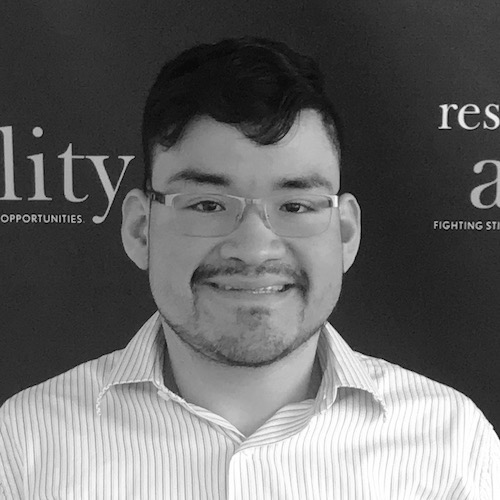 Steve Bobadilla smiling at the camera in front of the RespectAbility banner