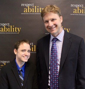 Derek Shields and RespectAbility Fellow Ryan Knight smiling in front of the RespectAbility banner