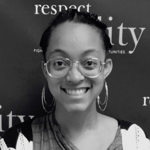 Naya Rhodes smiling in front of the RespectAbility banner