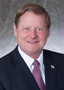 Steve Bartlett headshot in black suit, white shirt, red tie