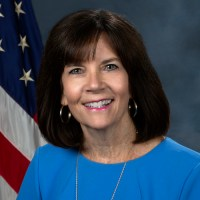 Mary Lazare smiling in front of an American flag