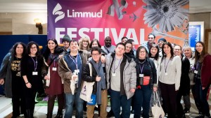 Members of the Limmud La'am Program with some Limmud Inclusion volunteers last year at Limmud Festival smiling together in front of a banner