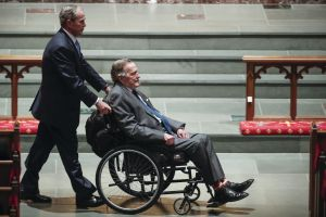 President George H.W. Bush wearing John's Crazy Socks to Barbara Bush's funeral. Bush is in a wheelchair being pushed by his son, President George W. Bush.