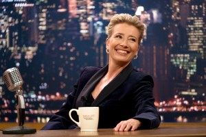Emma Thompson sits behind a late night talk show desk with a city skyline background and a mug in front of her